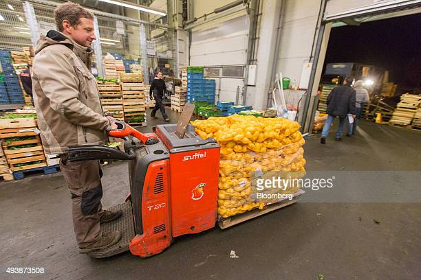 A customer uses a pallet truck to transport potatoes at the wholesale food market in Frankfurt Germany on Friday Oct 23 2015 Falling prices and...