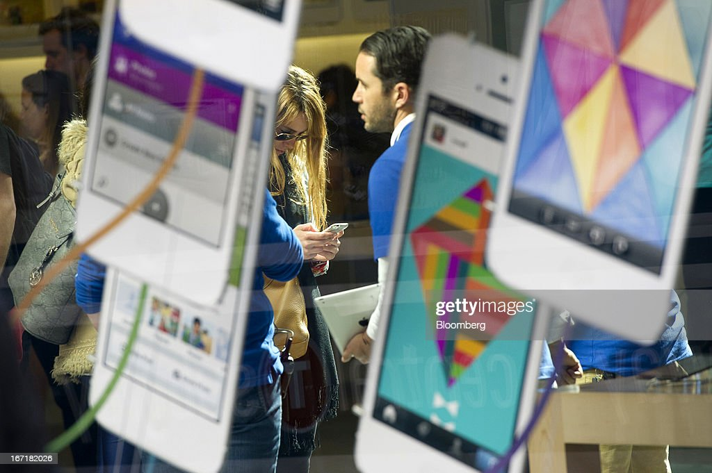 A customer uses a smart phone inside a store in San Francisco, California, U.S., on Friday, April 19, 2013. Apple Inc. is expected to release earnings data on April 23. Photographer: David Paul Morris/Bloomberg via Getty Images