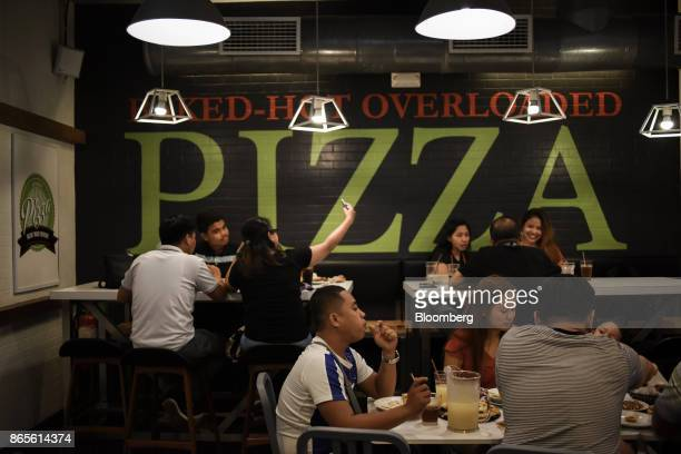 A customer uses a smart phone to take a selfie photograph as other diners eat at a Greenwich Pizzeria operated by Jollibee Foods Corp in the...