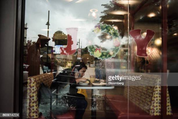 A customer uses a smart phone while dining inside a Jollibee Foods Corp restaurant in the Bonifacio Global City triangle area of Manila the...