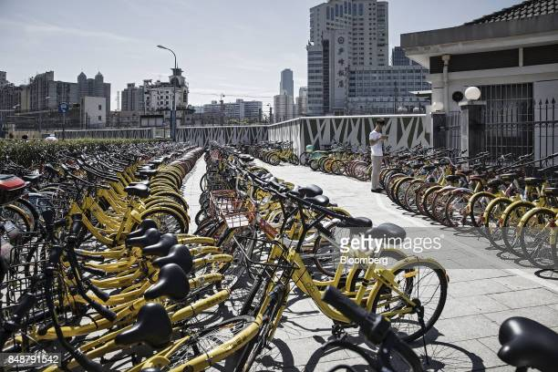 A customer uses a smartphone while selecting a bicycle at a designated parking space outside a subway station in Shanghai China on Thursday Sept 12...