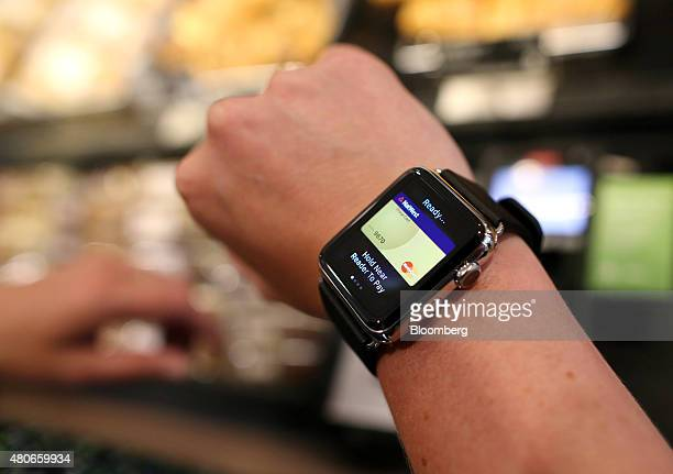 A customer uses an Apple Inc Apple Watch to pay via the Apple Pay system from their National Westminster Bank account at the checkout till inside a...