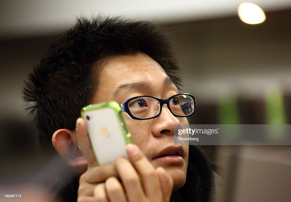 A customer uses an Apple Inc. iPhone 5 as he takes part in a workshop held at the company's store in the Wangfujing area of Beijing, China, on Tuesday, March 12, 2013. Apple's Wangfujing store is the largest in Asia. Photographer: Tomohiro Ohsumi/Bloomberg via Getty Images