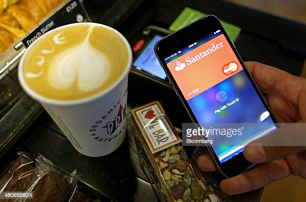 A customer uses an Apple Inc iPhone to pay via the Apple Pay system from their Santander account at the checkout till inside a Pret A Manger Ltd...