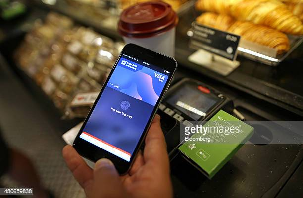 A customer uses an Apple Inc iPhone to pay via the Apple Pay system from their Royal Bank of Scotland account at the checkout till inside a Pret A...