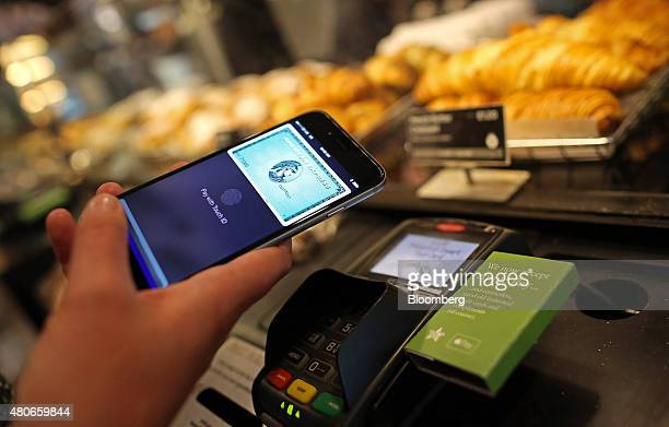 A customer uses an Apple Inc iPhone to pay via the Apple Pay system from their American Express Co account at the checkout till inside a Pret A...