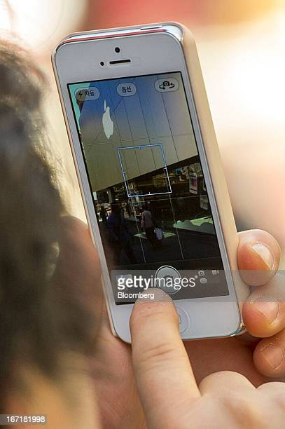 A customer uses an Apple Inc iPhone to take a photograph of the facade of an Apple Inc store in San Francisco California US on Friday April 19 2013...