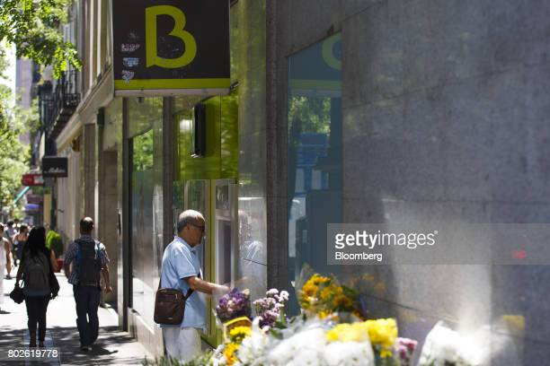 A customer uses an automated teller machine at a Bankia SA bank branch in Madrid on Wednesday June 28 2017 Bankia SA agreed to acquire Banco Mare...