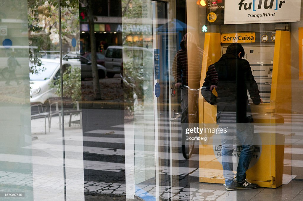 A customer uses an automated teller machine (ATM) at a CaixaBank SA branch in Sabadell, Spain, on Wednesday, Nov. 28, 2012. Spanish banks getting European aid will shrink their balance sheets more than 60 percent, the European Commission said, as BFA-Bankia, the biggest rescued lender, expects to lose 19 billion euros ($25 billion) this year. Photographer: Stefano Buonamici/Bloomberg via Getty Images