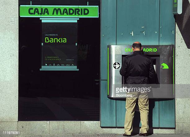 A customer uses an automated teller machine at a Caja Madrid bank branch advertising Bankia the new Spanish banking unit formed from the merger of...