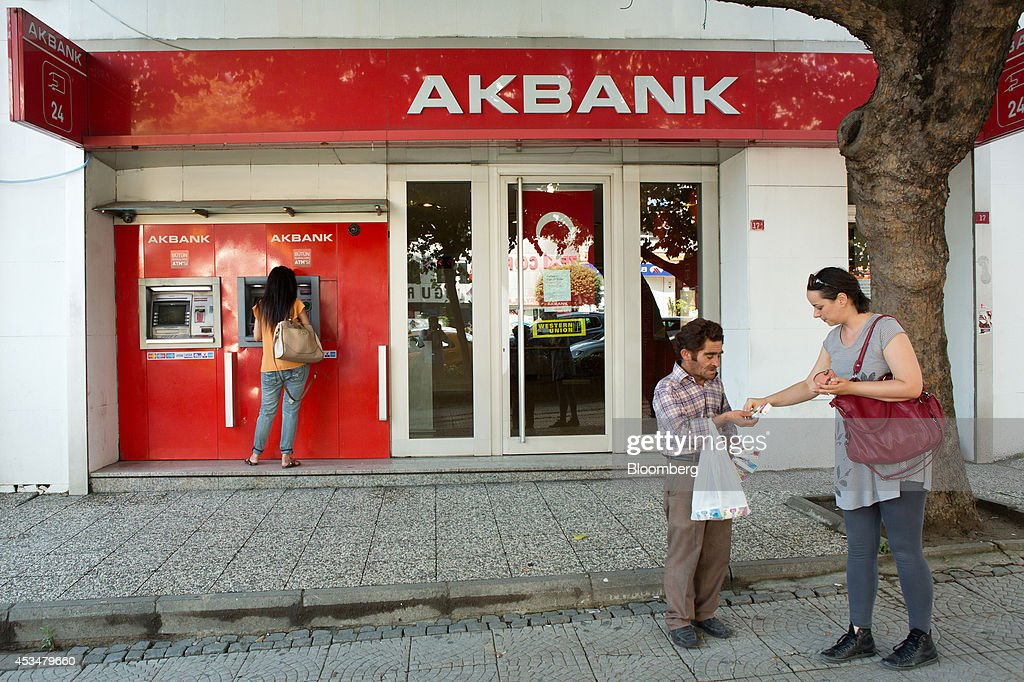 A customer uses an automated teller machine (ATM) operated by Akbank TAS in the Besiktas district of Istanbul, Turkey, on Sunday, Aug. 10, 2014. Investors said they will need to assess the next government's commitment to financial stability should Turkish Prime Minister Recep Tayyip Erdogan assume the presidency this month. Photographer: Kerem Uzel/Bloomberg via Getty Images