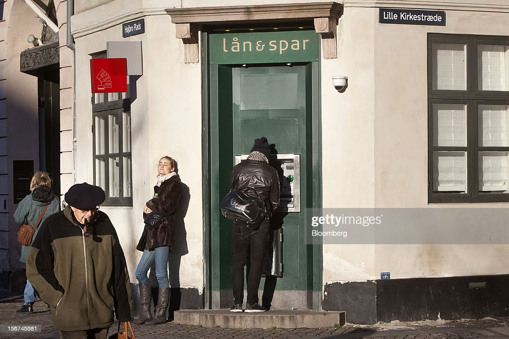 A customer uses an automated teller machine (ATM) operated by Lan & Spar Bank A/S in central Copenhagen, Denmark, on Monday, Nov. 19, 2012. Denmark's two-year yields sank to the lowest in almost three months in Copenhagen trading as Europe's debt crisis continues to drive investors north. Photographer: Linus Hook/Bloomberg via Getty Images