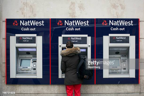 A customer uses an automated teller machine operated by NatWest bank part of the Royal Bank of Scotland Group Plc in London UK on Tuesday April 16...