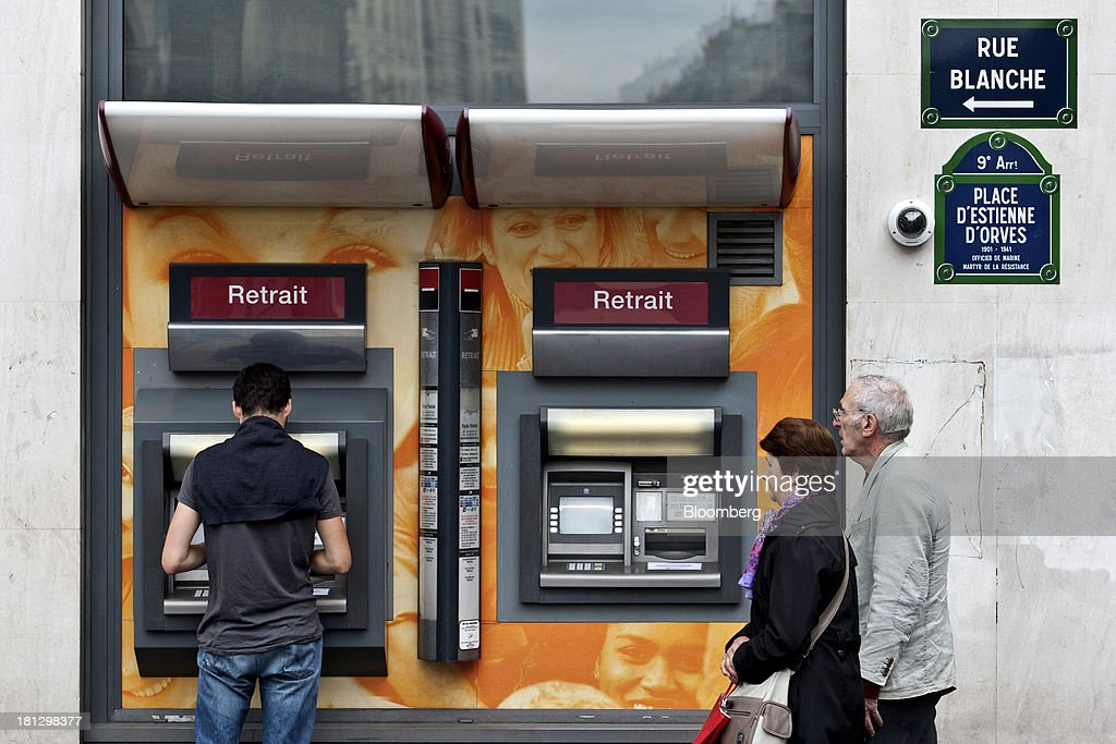 A customer uses an automated teller machine (ATM) operated by Societe Generale SA in Paris, France, on Thursday, Sept. 19, 2013. Bank of France General Council member Bernard Maris said France will end up restructuring its debt as tax 'optimization' by large companies including Google Inc. will leave too big a burden on the middle class. Photographer: Balint Porneczi/Bloomberg via Getty Images