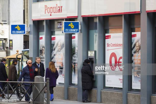 A customer uses an automated teller machine outside a Banco Popular Espanol SA bank branch in Madrid Spain on Friday Feb 10 2017 Banco Populars new...