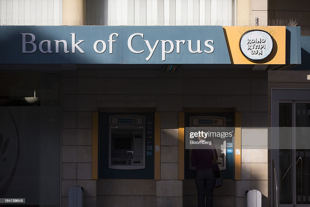 A customer uses an automated teller machine (ATM) outside a Bank of Cyprus Plc branch in Nicosia, Cyprus, on Wednesday, March 20, 2013. European policy makers weighed how far to push Cyprus after lawmakers in the Mediterranean nation rejected an unprecedented levy on bank deposits, throwing into limbo a rescue package designed to keep it in the euro. Photographer: Simon Dawson/Bloomberg via Getty Images