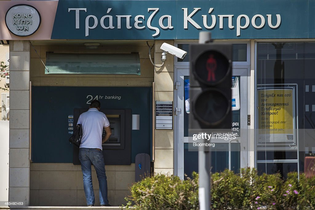 A customer uses an automated teller machine (ATM) outside a Bank of Cyprus Plc bank branch in Limassol, Cyprus, on Tuesday, April 8, 2014. Cyprus wants to shield financial flows with Russia, where it's the biggest foreign investor, as the U.S. and the European Union ratchet up sanctions in response to President Vladimir Putin's annexing Crimea from Ukraine. Photographer: Andrew Caballero-Reynolds/Bloomberg via Getty Images