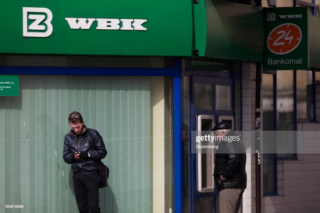 A customer uses an automated teller machine (ATM) outside a Bank Zachodni WBK SA branch in Wroclaw, Poland, on Monday, March 25, 2013. KBC Groep NV of Belgium and Banco Santander SA of Spain raised 4.89 billion zloty ($1.51 billion) from the sale of a stake in Bank Zachodni WBK SA, Poland's third-largest lender. Photographer: Bartek Sadowski/Bloomberg via Getty Images