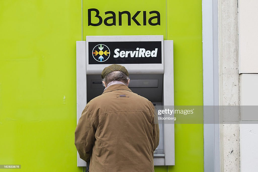 A customer uses an automated teller machine (ATM) outside a Bankia SA branch in Madrid, Spain, on Thursday, Feb. 28, 2013. BFA-Bankia Chairman Jose Ignacio Goirigolzarri said a balance sheet clean-up that inflicted a 21.2 billion-euro ($27.6 billion) after-tax loss last year will set the Spanish banking group on course to repay state aid. Photographer: Angel Navarrete/Bloomberg via Getty Images