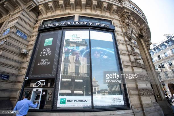 A customer uses an automated teller machine outside a BNP Paribas SA bank branch in Paris France on Tuesday July 18 2017 BNP Paribas agreed to pay...