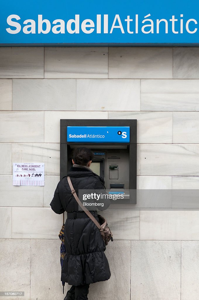 A customer uses an automated teller machine (ATM) outside a branch of Banco Sabadell SA in Sabadell, Spain, on Wednesday, Nov. 28, 2012. Spanish banks getting European aid will shrink their balance sheets more than 60 percent, the European Commission said, as BFA-Bankia, the biggest rescued lender, expects to lose 19 billion euros ($25 billion) this year. Photographer: Stefano Buonamici/Bloomberg via Getty Images
