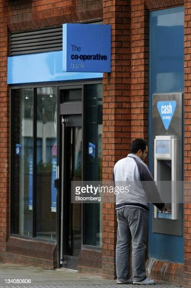 A customer uses an automated teller machine outside a branch of the CoOperative Bank Plc part of the CoOperative Group Ltd in Stockport UK on...