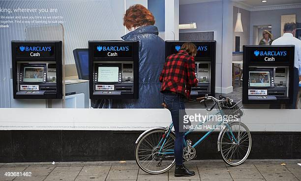 A customer uses an automated teller machine outside a branch of the British bank Barclays in London on October 22 2015 Britain's Competition and...
