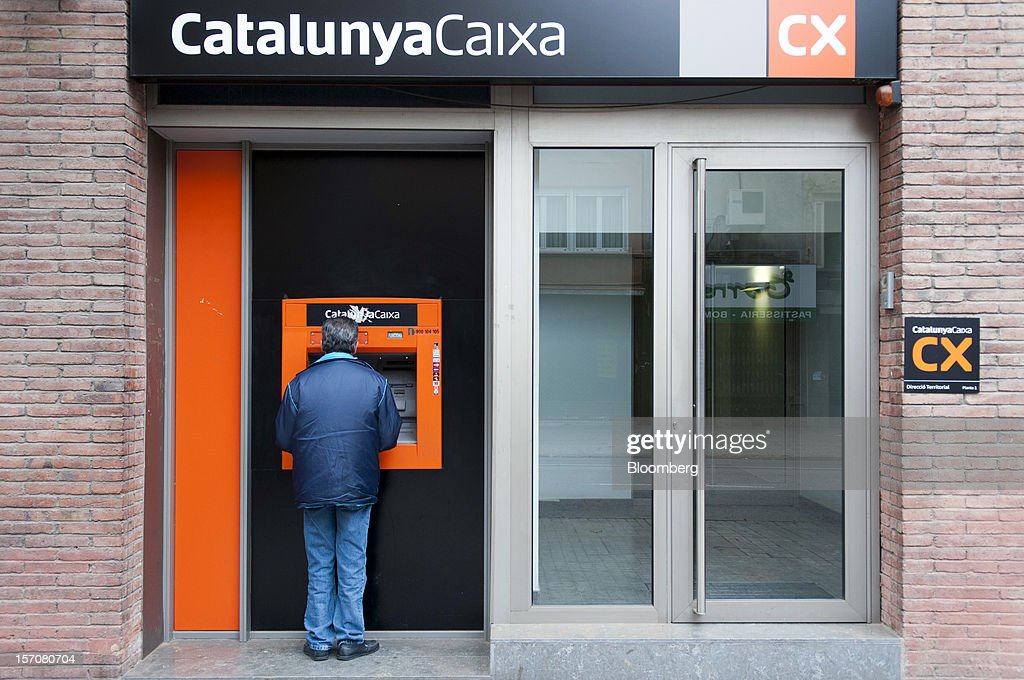 A customer uses an automated teller machine (ATM) outside a CatalunyaCaixa bank branch in Sabadell, Spain, on Wednesday, Nov. 28, 2012. Spanish banks getting European aid will shrink their balance sheets more than 60 percent, the European Commission said, as BFA-Bankia, the biggest rescued lender, expects to lose 19 billion euros ($25 billion) this year. Photographer: Stefano Buonamici/Bloomberg via Getty Images