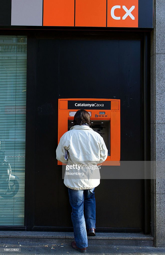 A customer uses an automated teller machine (ATM) outside a CatalunyaCaixa bank branch in Barcelona, Spain, on Tuesday, Jan. 8, 2013. Banco Santander SA, Spain's biggest lender, will offer 263 million euros ($345 million) in stock to buy out minority investors in its Banco Espanol de Credito SA retail unit and close 700 local branches to cut costs. Photographer: David Ramos/Bloomberg via Getty Images