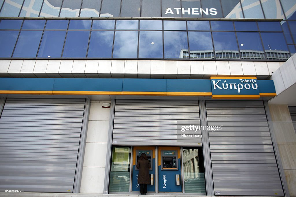 A customer uses an automated teller machine (ATM) outside a closed bank branch at the headquarters of the Bank of Cyprus Plc in Athens, Greece, on Tuesday, March 19, 2013. Cyprus's passage of an unprecedented levy on bank deposits was in doubt as euro-area finance ministers responded to criticism of the measure by loosening their stance on how the money is raised. Photographer: Kostas Tsironis/Bloomberg via Getty Images