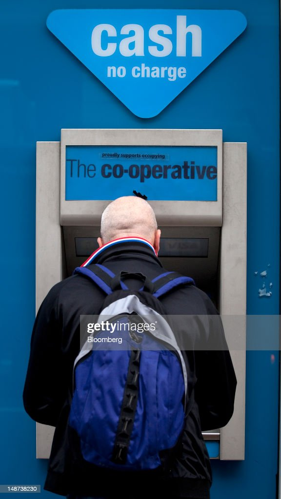 A customer uses an automated teller machine (ATM) outside a Co-Operative Bank Plc branch in London, U.K., on Thursday, July 19, 2012. Lloyds Banking Group Plc agreed to sell 632 branches to Co-Operative Bank Plc for an initial 350 million pounds ($548 million), as the U.K.'s biggest mortgage lender divests assets to comply with its government bailout. Photographer: Simon Dawson/Bloomberg via Getty Images