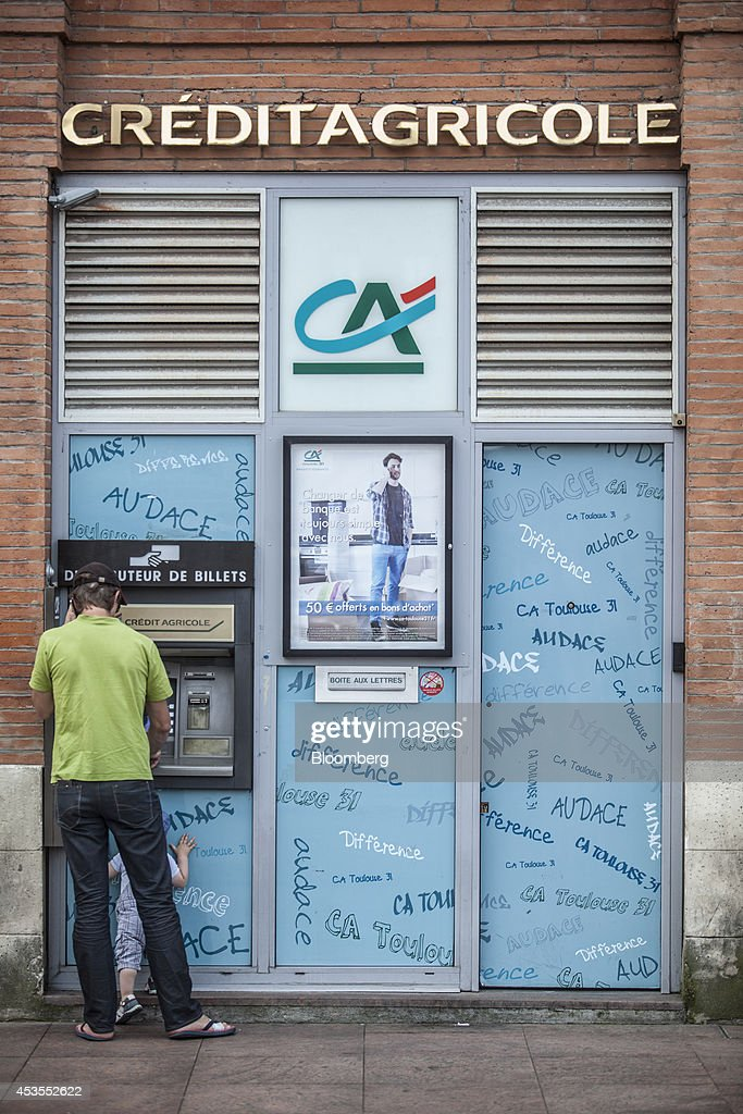 A customer uses an automated teller machine (ATM) outside a Credit Agricole SA bank branch in Toulouse, France, on Tuesday, Aug. 12, 2014. The euro traded 0.3 percent from a nine-month low before reports this week that may show growth in the region weakened and inflation slowed, adding to signs the bloc's economy is struggling to recover. Photographer: Balint Porneczi/Bloomberg via Getty Images