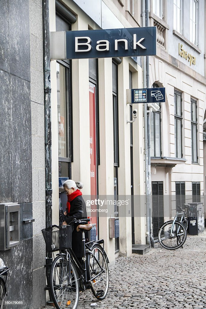 A customer uses an automated teller machine (ATM) outside a Danske Bank A/S branch in Copenhagen, Denmark, on Friday, Feb. 1, 2013. Danish regional banks are struggling to emerge from a burst property bubble that's forced the government resolution agency to take over a dozen lenders after losses on commercial and agricultural loans wiped out capital. Photographer: Freya Ingrid Morales/Bloomberg via Getty Images