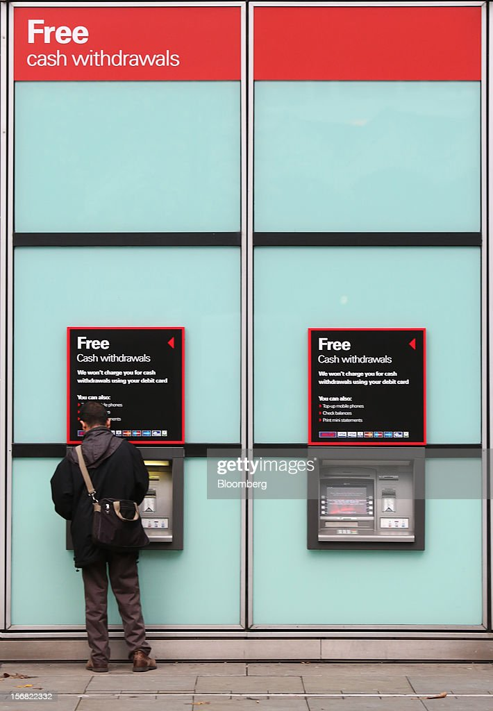 A customer uses an automated teller machine (ATM) outside a HSBC Holdings Plc bank branch in London, U.K., on Thursday, Nov. 22, 2012. Shares of HSBC have climbed 26 percent this year in London trading, and 30 percent in Hong Kong, as Chief Executive Officer Stuart Gulliver pared costs and sold assets to revive profit and focus on emerging economies in which the bank has a greater market share. Photographer: Chris Ratcliffe/Bloomberg via Getty Images