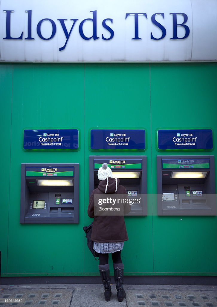 A customer uses an automated teller machine (ATM) outside a Lloyds TSB bank branch, part of the Lloyds Banking Group Plc, on Oxford Street in central London, U.K., on Monday, Feb. 25, 2013. U.K. Chancellor of the Exchequer George Osborne won't bow to opposition calls to change economic plans after the decision by Moody's Investors Service to strip the U.K. of its Aaa status. Photographer: Jason Alden/Bloomberg via Getty Images
