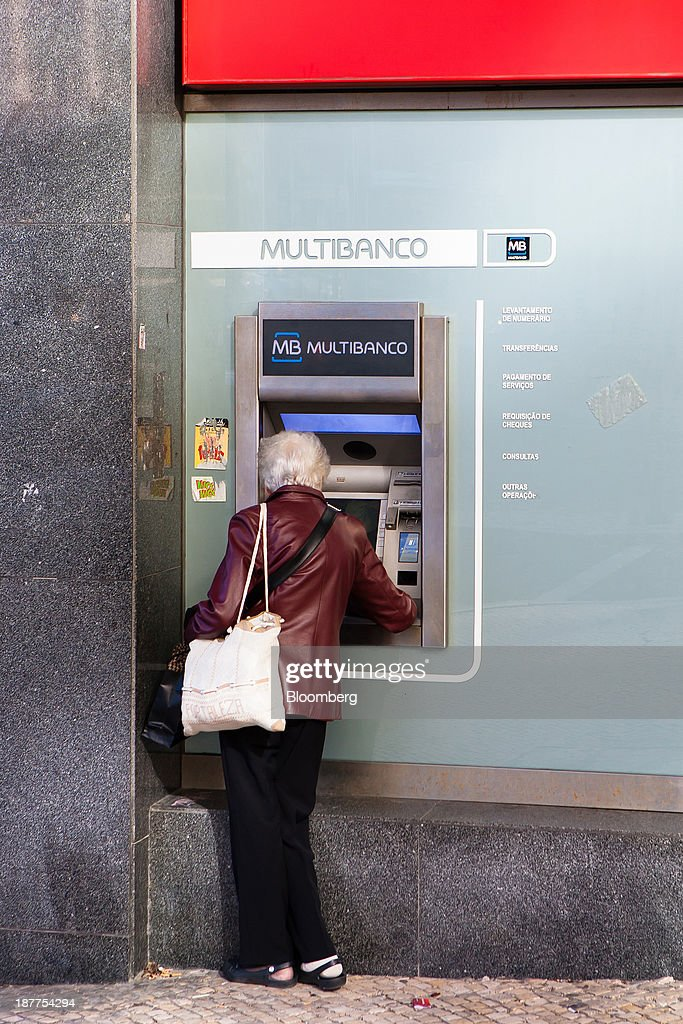 A customer uses an automated teller machine (ATM) outside a Santander Totta SA bank branch in Lisbon, Portugal, on Tuesday, Nov. 12, 2013. Portugal's jobless rate dropped for a second quarter, falling to 15.6 percent in the three months through September as the country's economy shows signs of recovery. Mario Proenca/Bloomberg via Getty Images