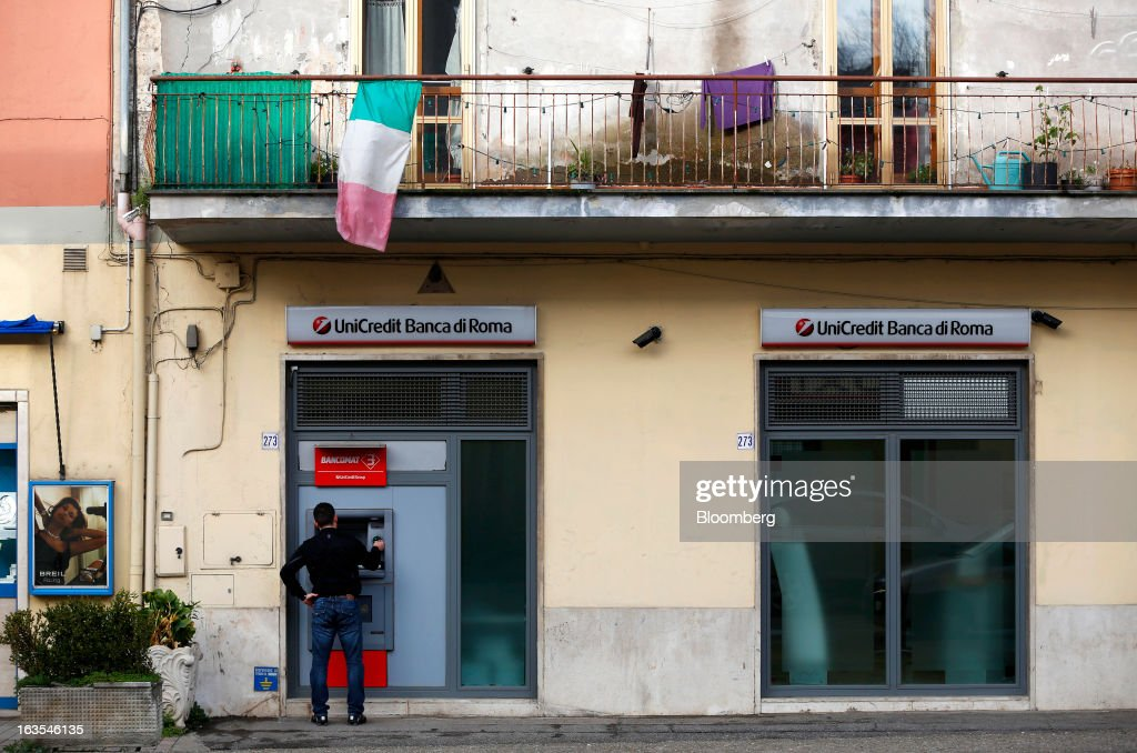 A customer uses an automated teller machine (ATM) outside a UniCredit SpA bank branch in Vetralla, Italy, on Monday, March 11, 2013. Intesa Sanpaolo SpA and UniCredit SpA are among Italian banks due to report losses for the fourth quarter this week, as the economic contraction meant more clients failed to repay their debts. Photographer: Alessia Pierdomenico/Bloomberg via Getty Images