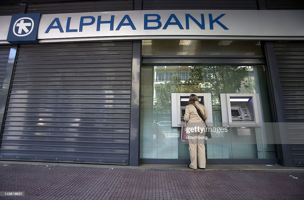 A customer uses an automated teller machine (ATM) outside an Alpha Bank AE branch in Athens, Greece, on Friday, May 4, 2012. European stocks dropped as investors awaited today's American payrolls report and elections in France, Greece, Italy and Germany this weekend. Photographer: Simon Dawson/Bloomberg via Getty Images