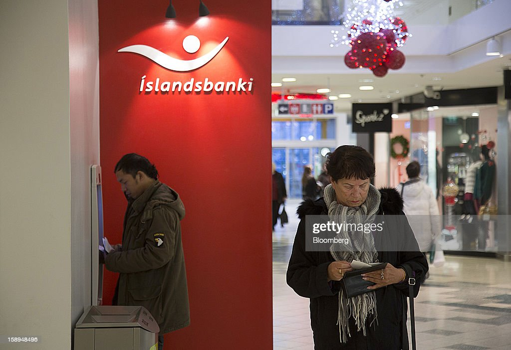 A customer uses an automated teller machine (ATM) outside an Islandsbanki hf bank branch inside a shopping center in Reykjavik, Iceland, on Wednesday, Jan. 2, 2013. Creditors of Iceland's three biggest failed banks are fighting for a waiver to krona controls imposed in 2008 amid risks pay-outs will be delayed beyond 2015. Photographer: Arnaldur Halldorsson/Bloomberg via Getty Images