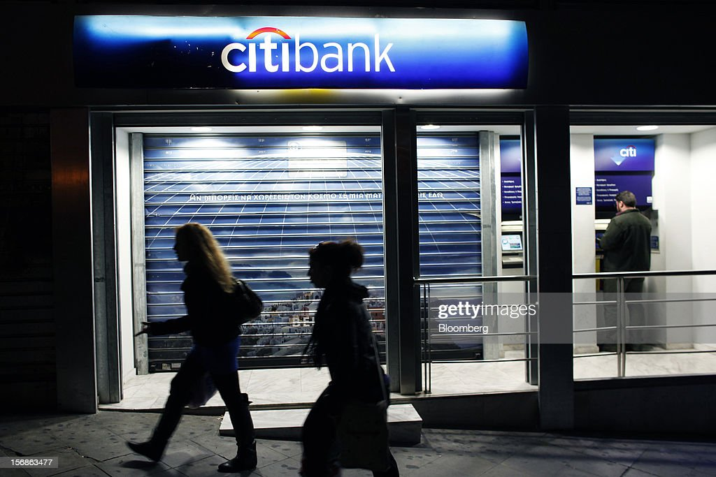 A customer uses an automated teller machine (ATM) while pedestrians pass an illuminated Citibank branch, operated by Citigroup Inc., in central Athens, Greece, on Thursday, Nov. 22, 2012. Citigroup Inc., the third-biggest U.S. bank by assets, said it will shutter almost half of its branches in Greece as European lawmakers continue a three-year struggle to fix the country's economy. Photographer: Angelos Tzortzinis/Bloomberg via Getty Images