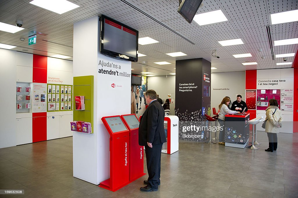 A customer uses an electronic information terminal inside a Vodafone Group Plc store in Barcelona, Spain, on Tuesday, Jan. 15, 2013. Vodafone Group Plc, the world's second largest mobile-phone company, plans to reduce the workforce at its Spanish unit as unemployment exceeding 25 percent in the recession-plagued country causes sales to drop. Photographer: David Ramos/Bloomberg via Getty Images