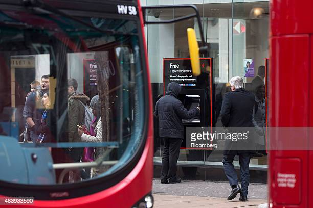A customer uses an HSBC automated teller machine as red London buses pass outside a bank branch operated by HSBC Holdings Plc in London UK on...