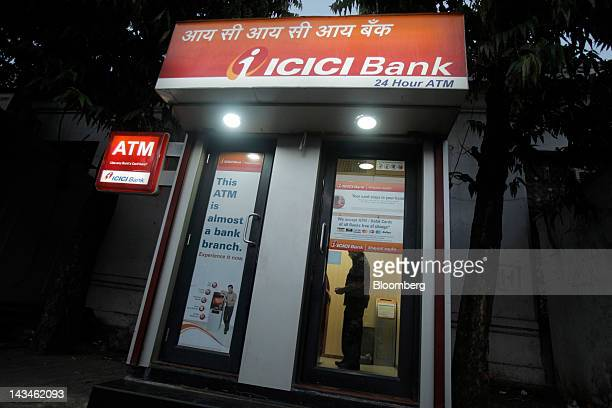 A customer uses an ICICI Bank Ltd automated teller machine in Mumbai India on Wednesday April 25 2012 Savings in India rose 134 percent in the year...