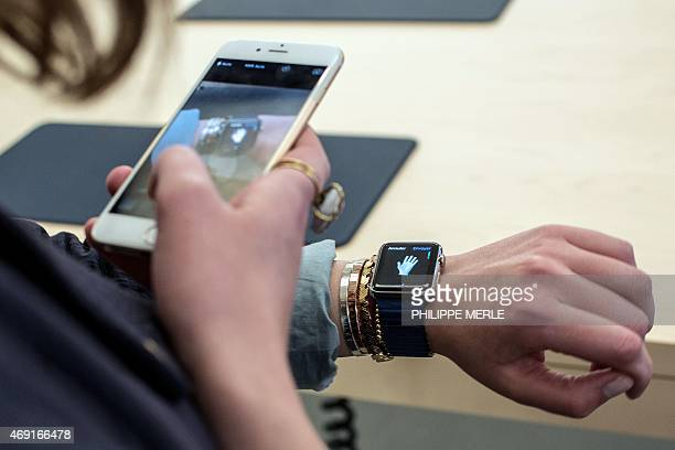 A customer uses an iPhone 6 smartphone to take a photo of a model of the Apple Watch during the device presentation at the Apple Store in Lyon...