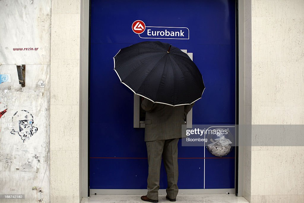 A customer uses an umbrella while using an automated teller machine (ATM) outside a Eurobank Ergasias SA branch in Athens, Greece, on Tuesday, May 14, 2013. Greek Prime Minister Antonis Samaras said the country can beat the targets set under its 240 billion-euro ($311 billion) International Monetary Fund and euro area bailout program and return to bond markets in the first half of next year. Photographer: Kostas Tsironis/Bloomberg via Getty Images