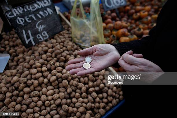 A customer uses euro coins to pay a farmer selling walnuts at his stall in a street market in Athens Greece on Thursday Nov 13 2014 Troika officials...