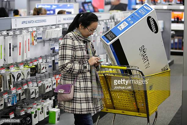 A customer uses her mobile phone as she shops for electronics and other items at a Best Buy on November 27 2015 in Skokie Illinois Many retail...