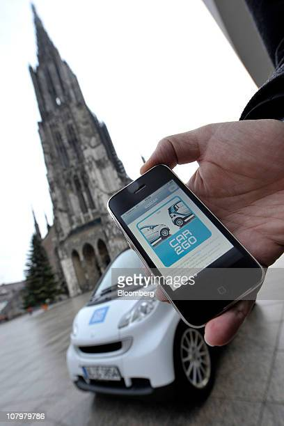 A customer uses his Apple Inc iPhone app to check the availability of a vehicle for Daimler AG's Car2go rental service in Ulm Germany on Monday Jan...