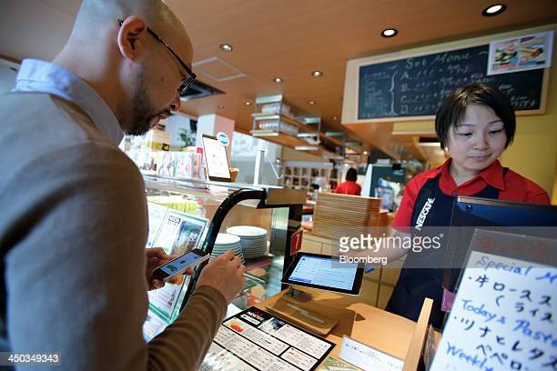 A customer uses PayPal Inc's mobile payment application on his Apple Inc iPhone to make a purchase during a promotional event at Nestle SA's Cafe...