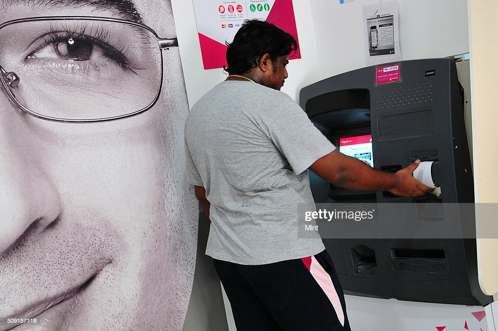 Customer using an ATM of Axis bank on July 9, 2014 in New Delhi, India.